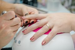 Putting varnish on nails. Processing of nails in beauty shop. Royalty Free Stock Photography