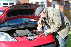 Putting water into a car radiator. Royalty Free Stock Image