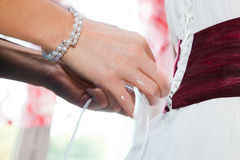 Putting on a wedding dress Stock Photo