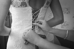 Putting wedding dress on. With the help of second person Stock Photography