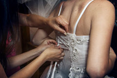 Putting wedding dress on Stock Images