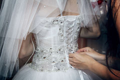 Putting wedding dress on Royalty Free Stock Photography