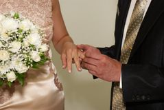 Putting on a wedding ring Royalty Free Stock Photo