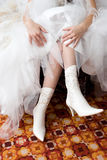 Putting on the white boots. Hands of the girl in a white wedding dress put on the white boots Royalty Free Stock Photo