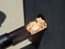 Putting Wood Chips in a Smoker. Putting Hickory Wood Chips in a Barbecue Smoker Stock Photography