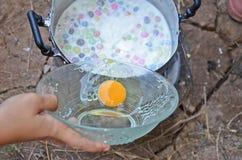 Putting yolk egg into sweet pot Stock Photography