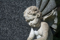 Putto or child angel statue as a grave stone on a cemetery Stock Photo