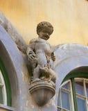 Putto in Sighisoara, Transylvania, Romania. Boy with piglet figure on a house in Sighisoara, Transylvania, Romania Stock Photo