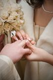 Puttting on a wedding ring Stock Photography