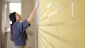Putty νέων κοριτσιών, κόλλα στον τοίχο, και ευθυγραμμίζει έπειτα putty στον τοίχο με το χέρι του Επισκευή, ομαλοί τοίχοι απόθεμα βίντεο