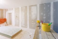 Putty το μαχαίρι, κίτρινοι κάδοι με την κόλλα και τους κυλίνδρους κόλλας στον ξύλινο πίνακα στο δωμάτιο είναι κάτω από την κατασκ στοκ φωτογραφία