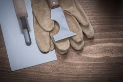 Putty knife plastering trowel and pair of leather working gloves Royalty Free Stock Photo