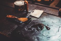 Putty knife on table with oil paint Stock Images