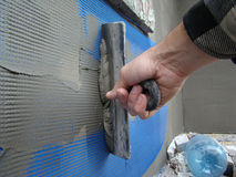 Putty. Ing reinforcing mesh  for exterior works with the spatula Stock Photo