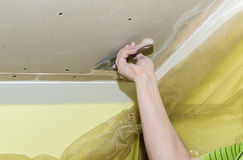 Puttying drywall seams. Builder embeds the joints drywall putty, close-up Royalty Free Stock Photography