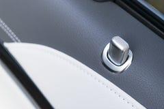 Puxador da porta com os botões do controle do fechamento de um automóvel de passageiros luxuoso Interior de couro preto do carro  imagem de stock royalty free