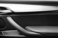 Puxador da porta com os botões do controle da janela de poder de um automóvel de passageiros luxuoso Interior de couro preto do c imagem de stock