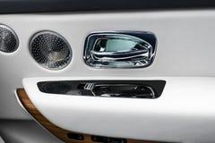 Puxador da porta com os botões do controle da janela de poder de um automóvel de passageiros luxuoso O branco perfurou o interior fotografia de stock royalty free