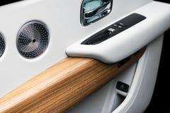Puxador da porta com os botões do controle da janela de poder de um automóvel de passageiros luxuoso O branco perfurou o interior imagem de stock