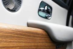 Puxador da porta com os botões do controle da janela de poder de um automóvel de passageiros luxuoso O branco perfurou o interior fotos de stock royalty free