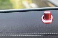 Puxador da porta com os botões vermelhos do controle do fechamento de um automóvel de passageiros luxuoso Interior de couro preto Foto de Stock Royalty Free