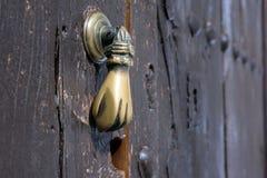Puxador da porta de bronze velho na forma de uma mão Porta de madeira de Brown de uma casa na cidade espanhola de Ronda imagem de stock