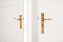 Puxador da porta dourado em portas brancas velhas Imagens de Stock