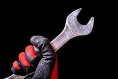 Puxe a ferramenta à disposição com as luvas protetoras isoladas no fundo preto fotos de stock