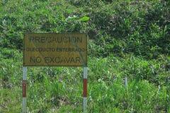 Puyo, Ecuador, 24-5-2019: muestra que advierte para no cavar debido al presente del tubo de aceite aqu? foto de archivo libre de regalías