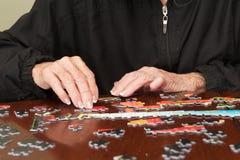 Puzzel die door een elderyvrouw wordt samengebracht Royalty-vrije Stock Afbeelding