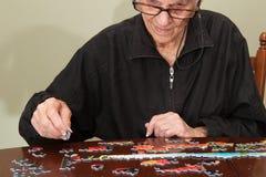 Puzzel die door een elderyvrouw wordt samengebracht Royalty-vrije Stock Foto's