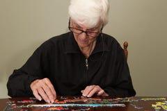 Puzzel die door een elderyvrouw wordt samengebracht Stock Fotografie