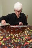 Puzzel die door een elderyvrouw wordt samengebracht Royalty-vrije Stock Fotografie