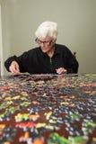 Puzzel die door een elderyvrouw wordt samengebracht Stock Foto's