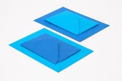 Puzzel van grote en kleine blauwe enveloppen op het witte lusje Stock Afbeelding