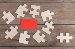 Puzzelstukken op houten achtergrond stock afbeeldingen