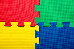 Puzzle. Interlocking foam puzzle pieces form four corners in bright colors Royalty Free Stock Photography