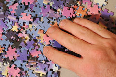 Puzzle. Close up of hand playing colored puzzle royalty free stock photography