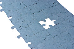 Puzzle. Blue puzzle with one piece missing isolated on a white background Stock Image