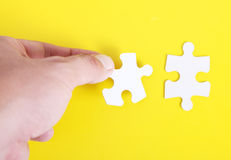 Puzzle. One hand clasping pieces of a puzzle over yellow background Stock Photo