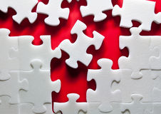 Puzzle. White puzzles on a red background Royalty Free Stock Photo