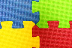 Puzzle. Interlocking foam puzzle pieces form four corners in bright colors Royalty Free Stock Photo