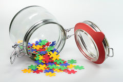 Puzzle. From a jar puzzle elements are distributed Stock Photo