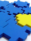 Puzzle. One yellow colour puzzle against blue colour puzzles Royalty Free Stock Photography