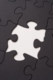Puzzle. A black puzzle with one piece missing in the center Stock Images