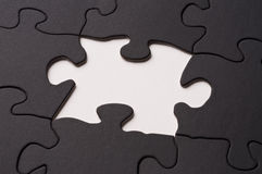Puzzle. A black puzzle with one piece missing in the center Royalty Free Stock Photos