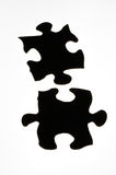 Puzzle. Two black silhouetted puzzle pieces Royalty Free Stock Photo