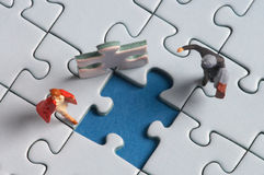 On puzzle. Two plasticfigures standing on a puzzle with a hole in it Stock Photo