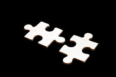 Puzzle. Two white puzzle black background isolate royalty free stock photography