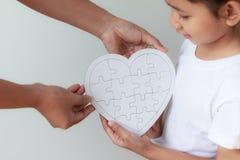 Puzzle asiatico della presa della bambina da sua madre per la famiglia Immagine Stock Libera da Diritti